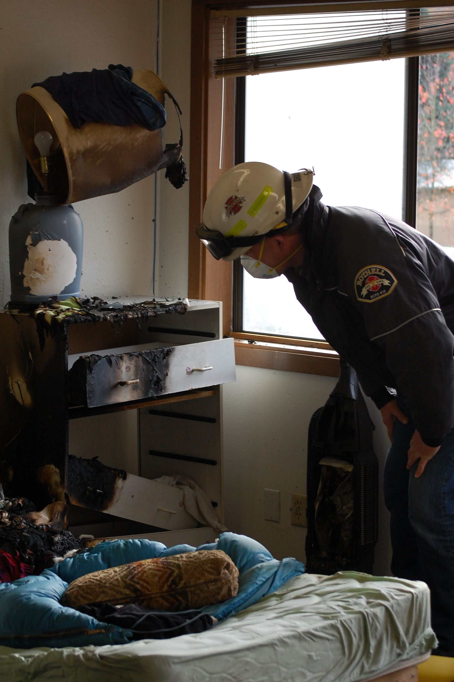 Member of the Fire Department investigating the aftermath of a fire in a home.