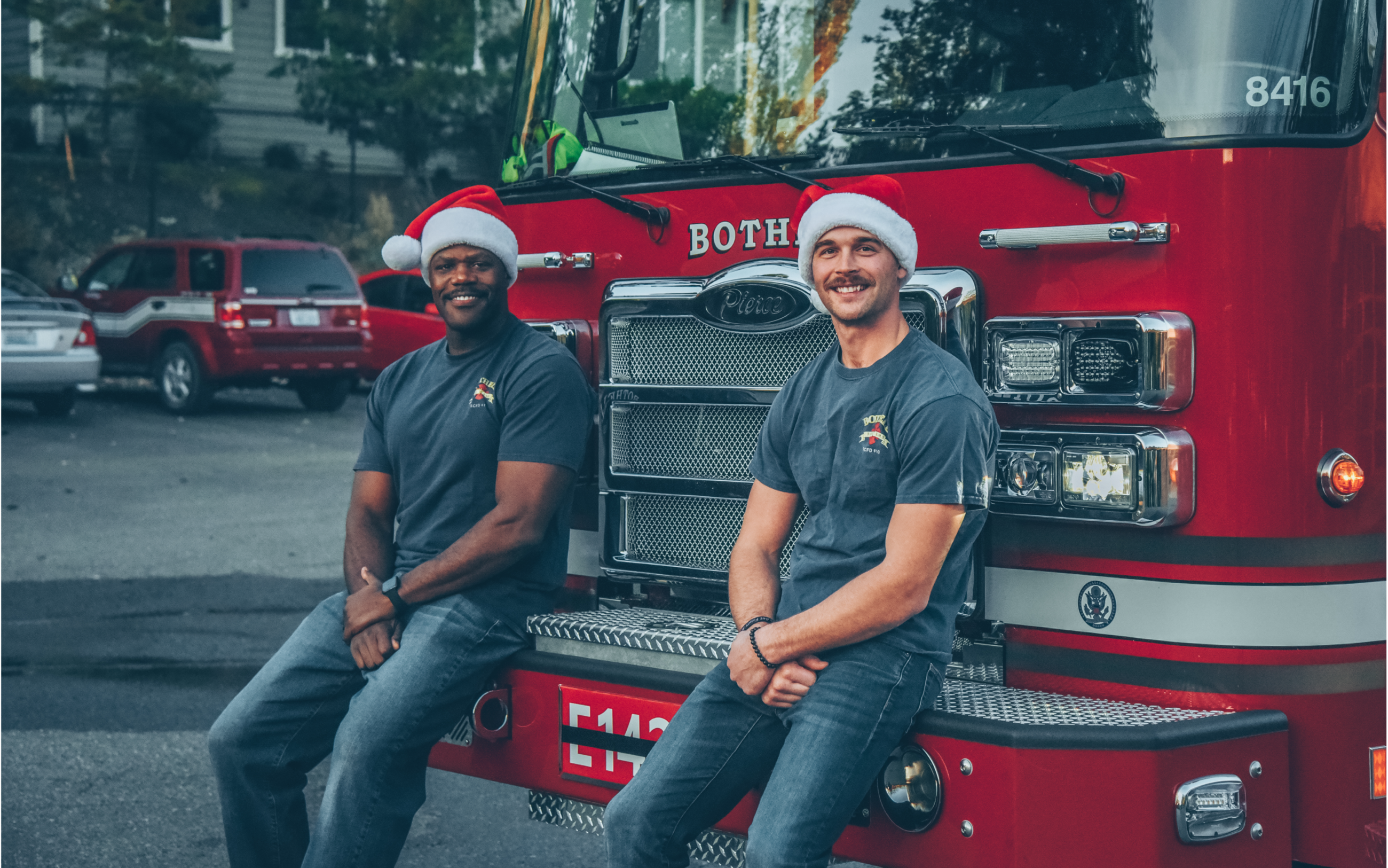 image of two bothell firefighters in santa hats